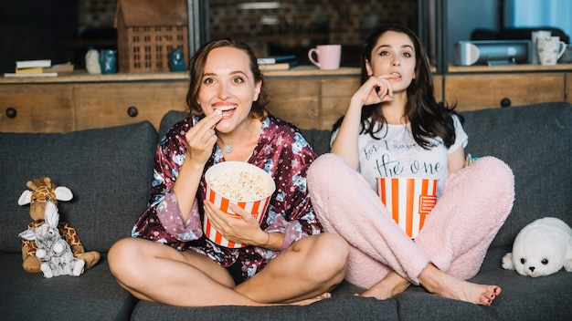 Two female friends watching television at home