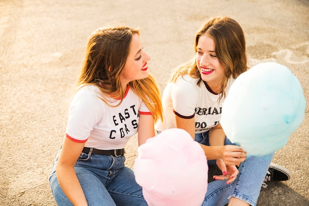 Two female friends with candy floss looking at each other