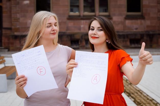 キャンパスの屋外に座っている異なるテスト結果を持つ2人の女性の友人