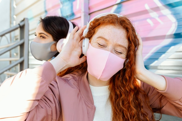 Two female friends with face masks outdoors listening to music on headphones