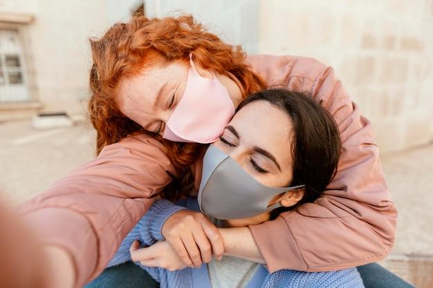 屋外でセルフィーを撮っているフェイスマスクを持つ2人の女性の友人