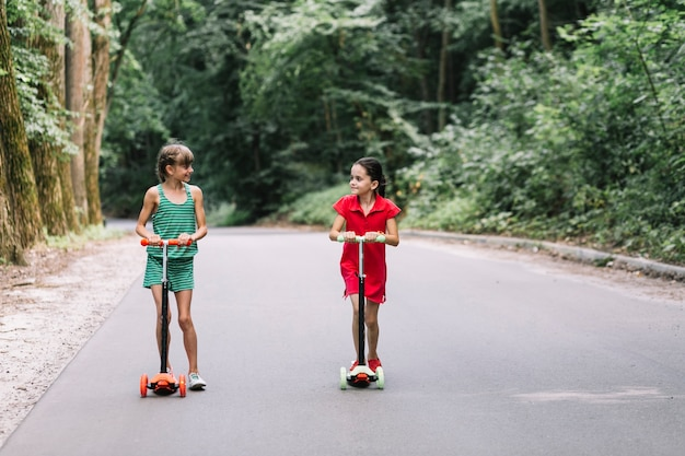 Due amici femminili con i motorini che se lo esaminano sulla strada