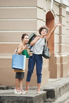 Two female friends with shopping bags catching taxi in the street