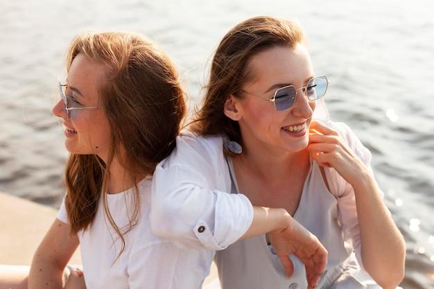 Две подруги в солнцезащитных очках веселятся у озера