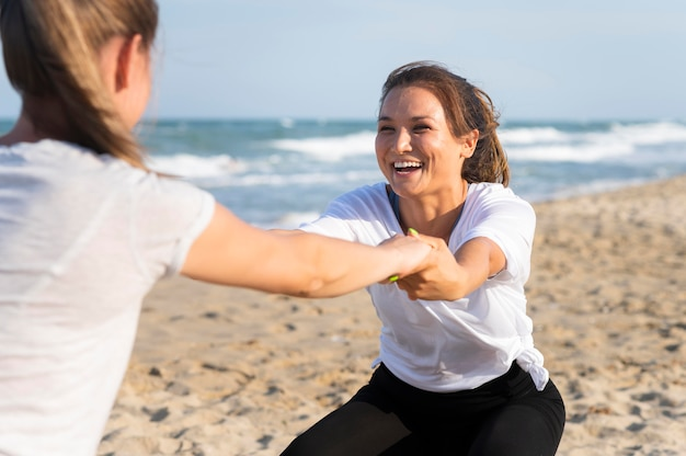 Two female friends working out together on the beach