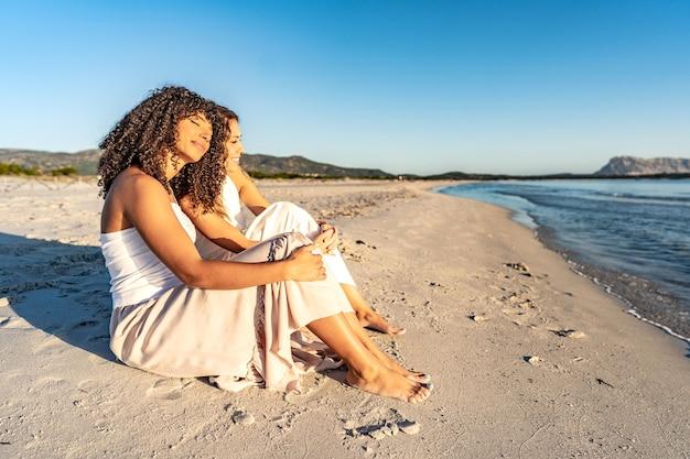 夕焼けや夜明けのロマンチックなシーンで隣同士のビーチに座って愛情を込めて暖める太陽を見ている2人の女性のガールフレンド。休暇中の自由奔放に生きるレズビアンのカップルは海や海の自然を楽しむ