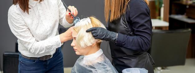 Две девушки-парикмахеры красят волосы молодой кавказской женщины в парикмахерской