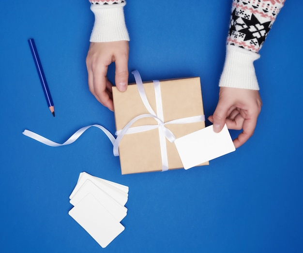 Two female hands are holding a cardboard gift square box tied with a white ribbon and empty paper business cards