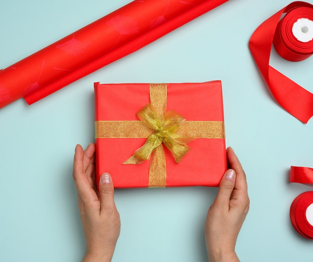 Two female hands are holding red gift box on a blue background, concept of congratulations