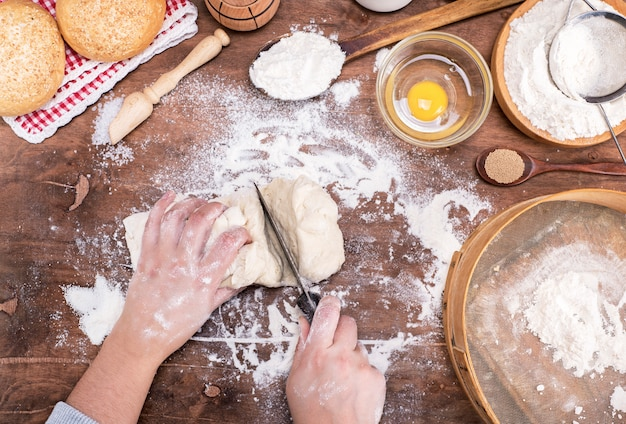 Two female hands cut with a knife yeast dough into pieces