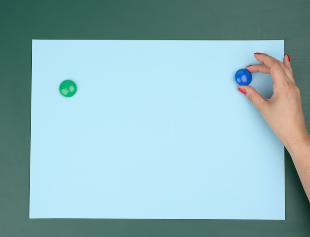 Two female hands fix a blue blank sheet of paper on a magnetic board,  place for an inscription