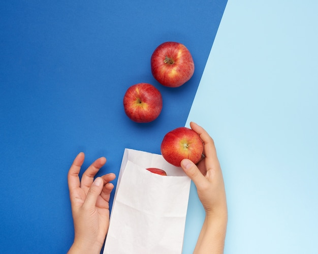 Two female hands fold ripe red apples in a white paper bag