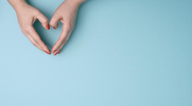두 여성의 손을 파란색 표면에 심장의 모양에 접혀. 감사와 친절 개념, 배너, 복사 공간