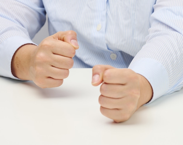Two female hands folded into a fist on a white table. strict leader, aggression and pressure on the person
