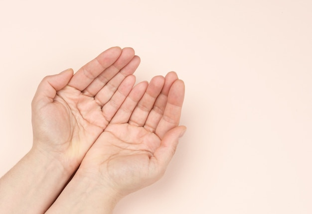 Two female hands folded palm to palm on a beige background, top view