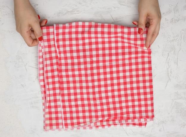 Две женские руки держат мятую бело-красную клетчатую текстильную кухонную салфетку на белом столе, вид сверху