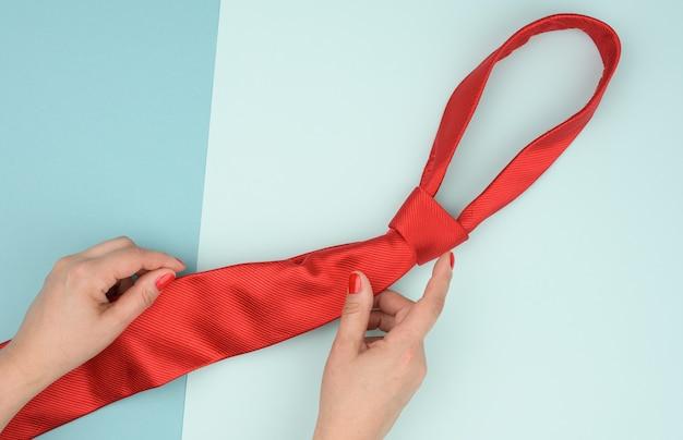2つの女性の手は青い背景に赤い絹のネクタイを保持します