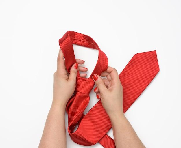 2つの女性の手が赤い絹のネクタイを持っています