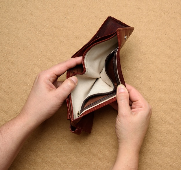 Two female hands hold brown leather open empty wallet for cash, top view