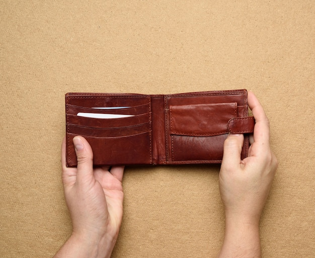 Two female hands hold brown leather open wallet for cash, top view