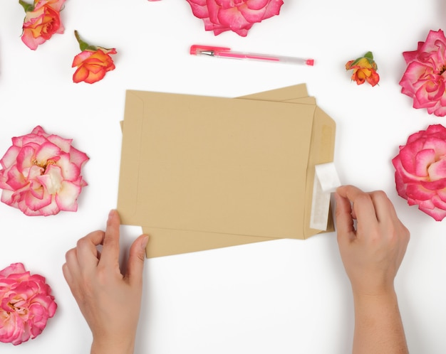 Two female hands hold a brown paper envelope