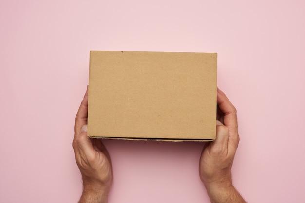 Две женские руки держат закрытую коричневую бумажную коробку на розовом