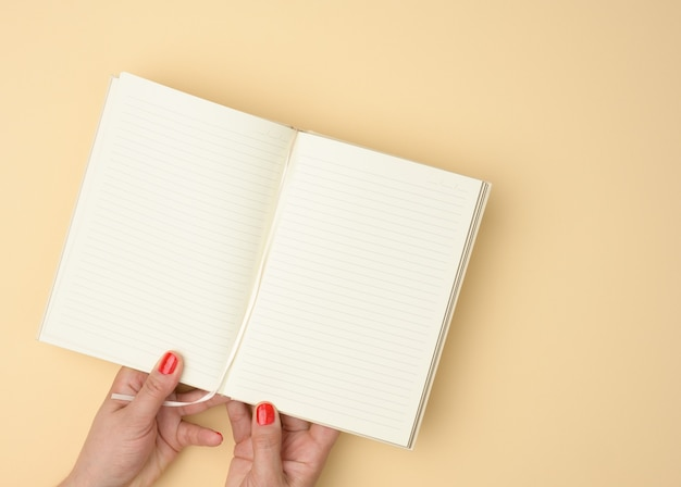 Two female hands hold an open notebook with blank white sheets on a beige background, top view