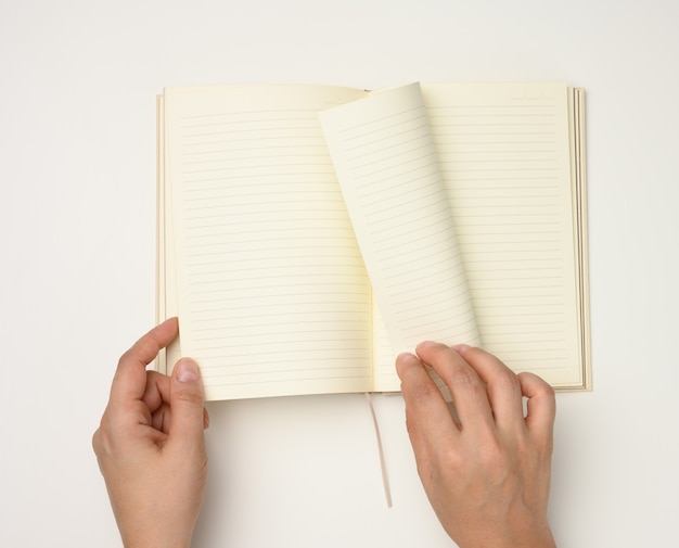 Two female hands hold an open notebook with blank white sheets on a white background, top view