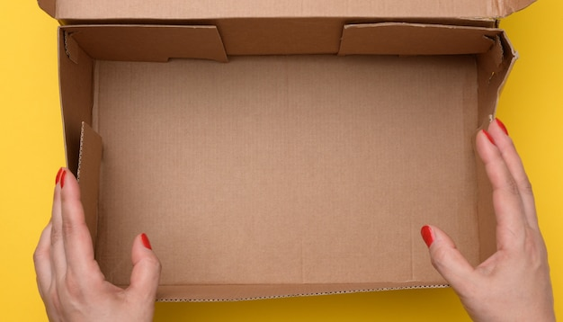 Two female hands hold open paper box on a yellow background, top view