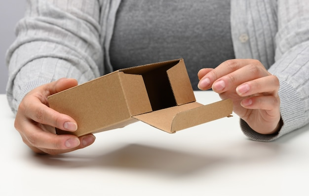 Two female hands hold a square box made of brown corrugated cardboard on a white background, close up