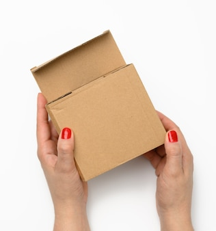 Two female hands hold a square box made of brown corrugated cardboard on a white background