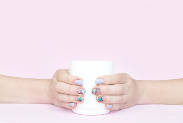 Two female hands hold white cup on pink background