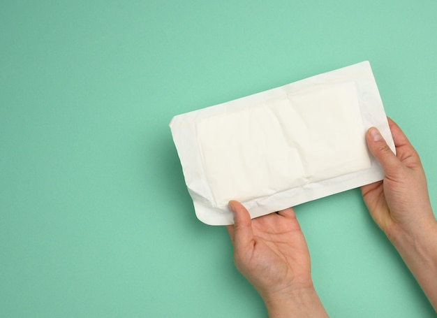 Two female hands hold white paper packaging with sterile medical gloves