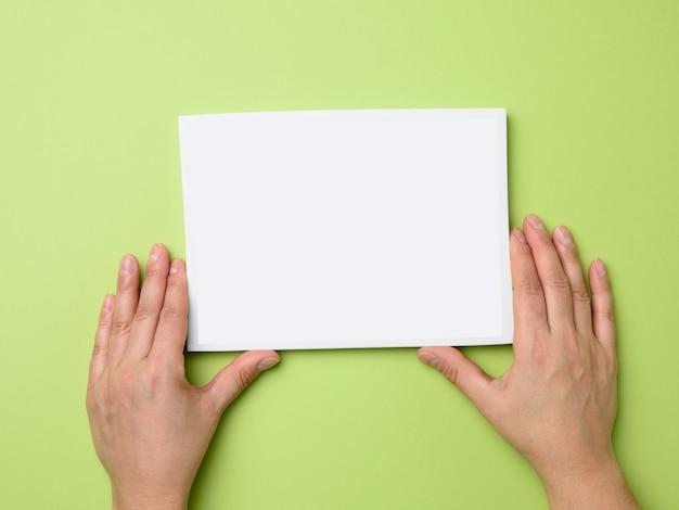 緑に空の白いフレームを保持している2つの女性の手