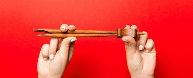 Two female hands holding chopsticks