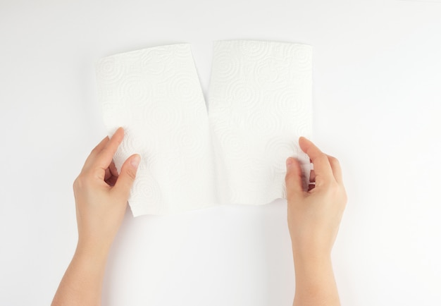Two female hands holding a clean white paper napkin for face and body