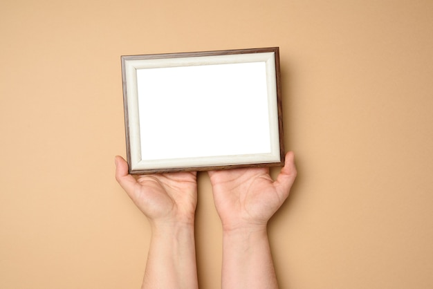 Two female hands holding a empty rectangular blank wooden frame, beige background