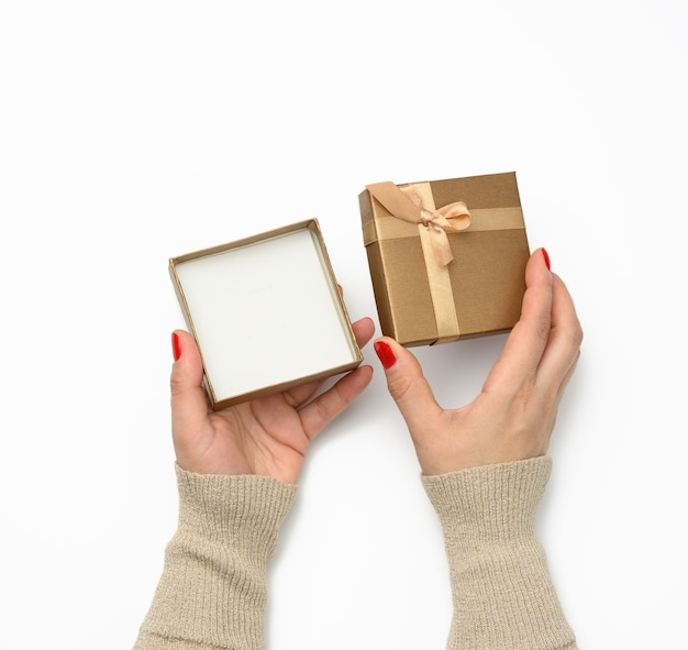 Two female hands holding a open empty square golden gift box with a bow