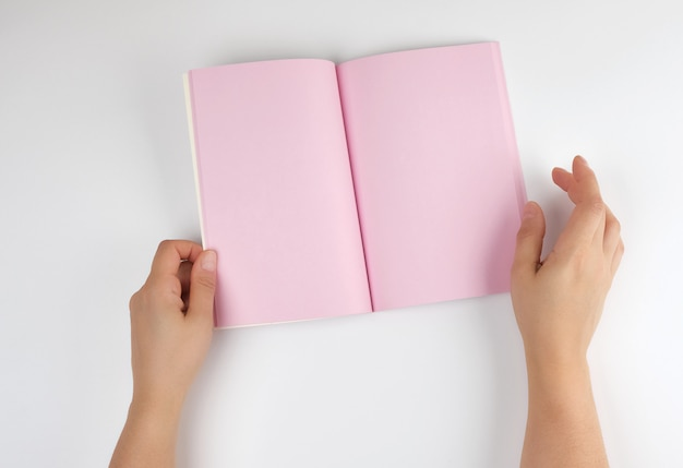 Two female hands holding open notepad with clean pink sheets