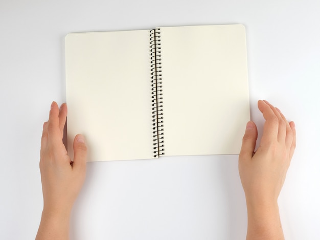 Two female hands holding open notepad with clean sheets