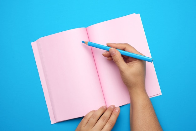 Two female hands holding open notepad with empty pink sheets, top view