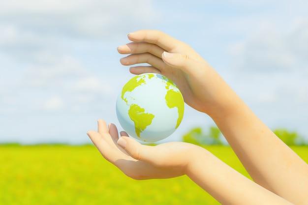 空と緑のフィールドのぼやけた背景を持つ惑星地球を保持している2つの女性の手。環境の概念。 3dレンダリング