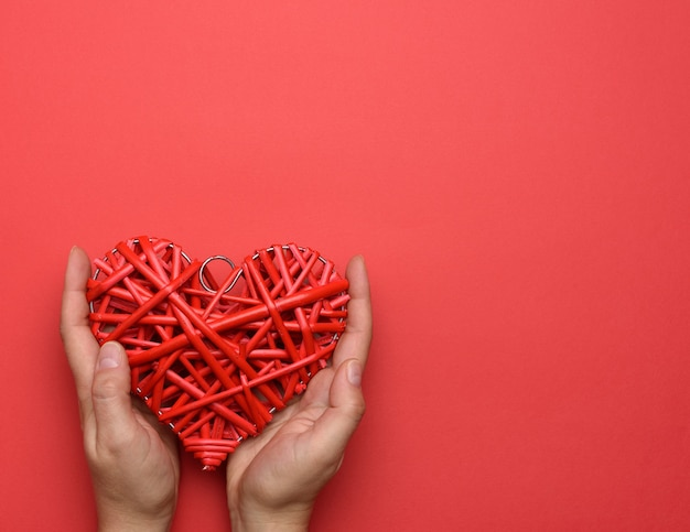 Two female hands holding a red wicker heart on red, love and kindness concept, copy space