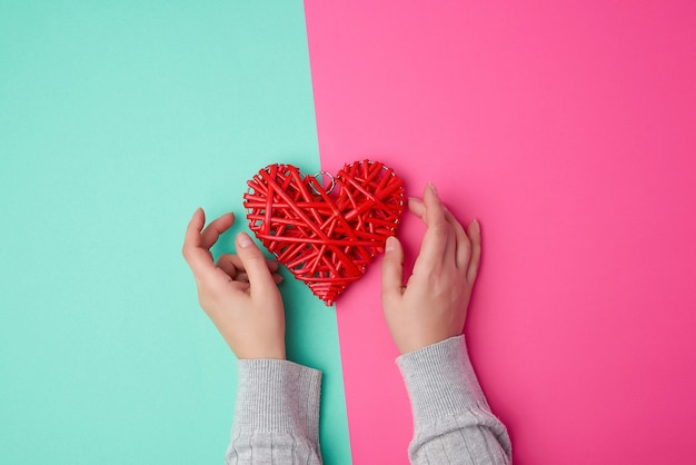 Two female hands holding a red wicker heart a symbol of love