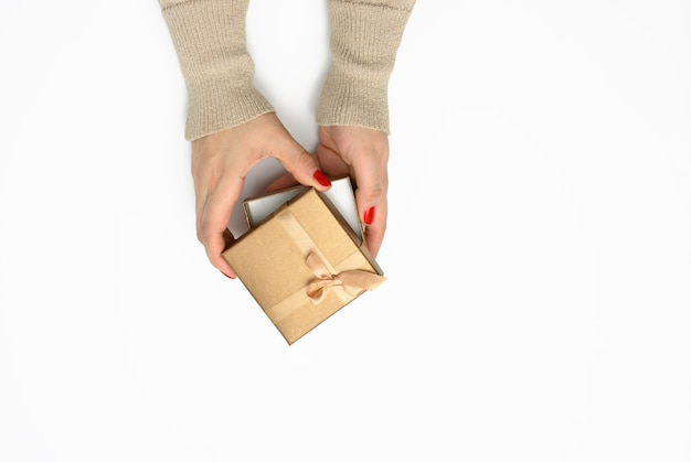 Two female hands holding a square golden gift box with a bow on a white background, concept of gratitude, birthday
