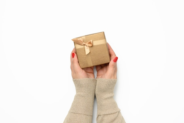Two female hands holding a square golden gift box with a bow on a white background