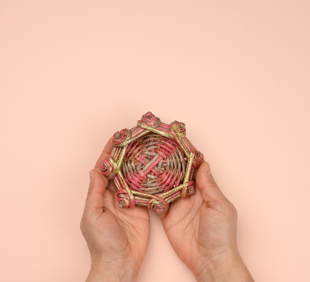 Two female hands holding a wicker wooden miniature decorative nest, top view
