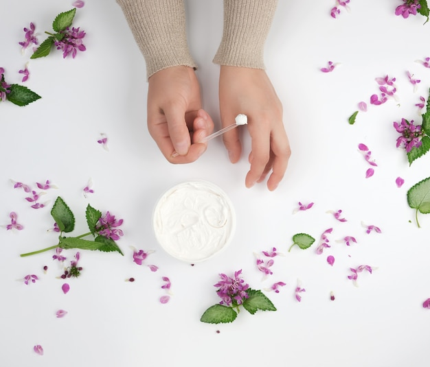 Two female hands and a jar with thick cream
