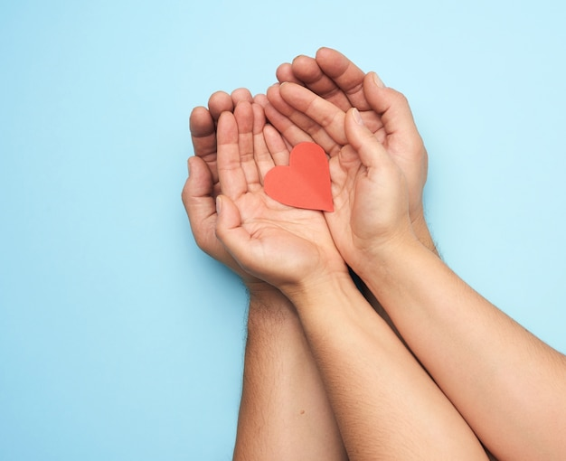 Two female hands lie in male palms and hold a red paper heart, top view. concept of kindness, love and donation