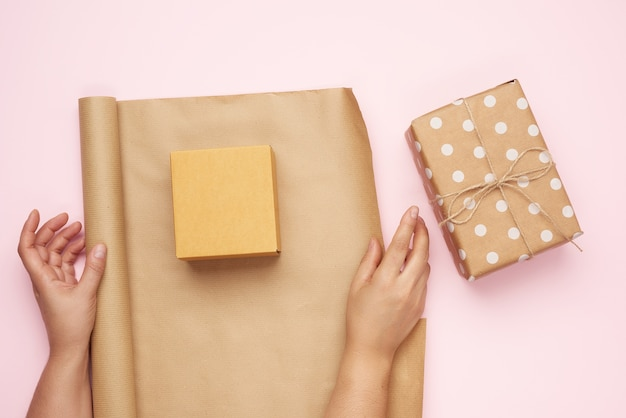 Two female hands pack gifts in brown kraft paper on pink